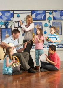 Teachers Playing Guitar With Pupils Having Music Lesson In Classroom